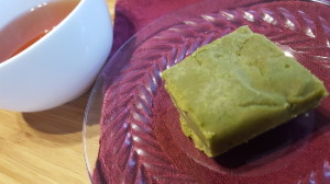 Matcha peanut butter fudge on a plate with tea in background.